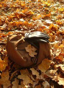 Torebka i rękawiczki na tle liści